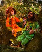 two fairy tale dwarf figures sitting on moos in woodland - stock photo