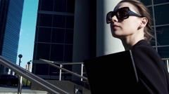 Portrait attractive successful business woman in sunglasses walking in city Stock Footage