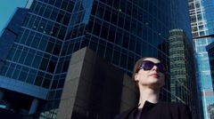 Ambitious young business woman in black walking in the city Stock Footage