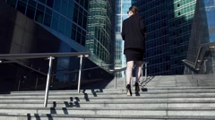 Young attractive motivated business woman walking up the stairs to city center Stock Footage