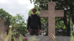 Man Prays In a Tomb With Cross Monument Stock Footage