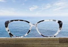 Glasses on a wooden table in front of the sea Stock Photos