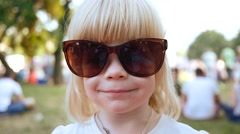 Cute little child blonde girl portrait in slow motion in big sun mother glasses Stock Footage
