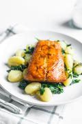 Grilled salmon with gnocchi and greens Stock Photos