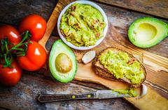 Guacamaole With Bread And Avocado On Rustic Wooden Background - stock photo