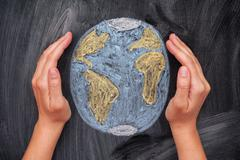 Hands protecting Planet Earth on black chalkboard background Stock Photos