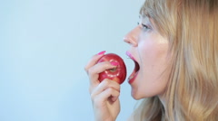 Beautiful girl eats a red apple on a blue Stock Footage