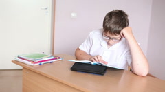Boy student reading a paragraph in the textbook sitting at a school desk Stock Footage