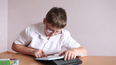 boy student reading a paragraph in the textbook sitting at a school desk - stock footage