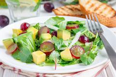Vegetarian salad with avocado, grape, rucola, onion, vinegar dressing Stock Photos