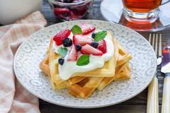 Homemade belgian waffles with yogurt, strawberry and blueberry, breakfast tim Stock Photos