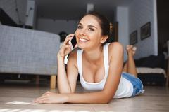 Beautiful smiling young woman talking on phone laying down at the floor in the - stock photo