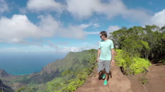 Active young man hiking along the high mountain ridge in lush volcanic canyon Stock Footage