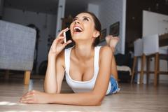 Beautiful laughing young woman talking on phone laying down at the floor in the Stock Photos