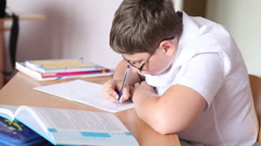 Student in glasses writes in a notebook sitting at a desk. Stock Footage
