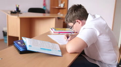 Teen student writing assignment in a notebook sitting at a desk. Stock Footage