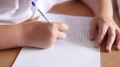 Boy writes in a notebook sitting at a desk. hands closeup Stock Footage