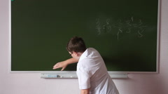 Teenager schoolboy wipes a blackboard to solve the example. Stock Footage