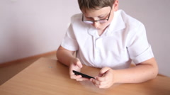 Teenager schoolboy playing phone sitting at the desk in the classroom. Stock Footage