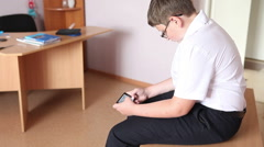 Teen boy playing phone sitting on the desk in the classroom. Stock Footage