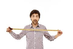 Portrait of handsome amused young man with tape measure Stock Photos