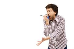 Portrait of handsome amused young man screaming in walkie-talkie - stock photo