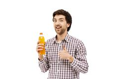 Young handsome cheerful man holding plastic bottle with orange b Stock Photos