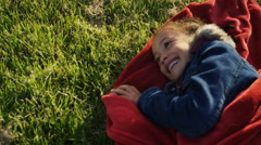 4K Young girl on a blanket on grass laughing wildly, in slow motion - stock footage