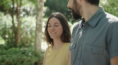 Young couple walking in the park. She talks and laughs. Dolly shot. Stock Footage