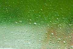 drops of water flow down on glass - stock photo