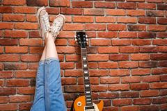 Close up of girl's legs and guitar over brick background Stock Photos