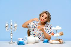 Portrait of young beautiful girl with sweets over blue background Stock Photos