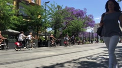 People walking and cycling at the Calle San Fernando in Seville - stock footage