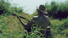 Back look of young boy in sunglasses and hat playing the guitar near lake. 4k Stock Footage