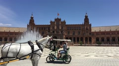 Horse and carriages driving around the Fountain at the Plaza de Espana Stock Footage