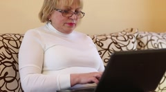 Woman with black laptop. Blonde woman types text uses notebook Stock Footage