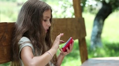 Teen girl sits on the bench in garden and uses red smartphone - stock footage