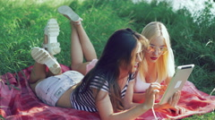 Brunette and blonde lying on blankets on the grass and using the tablet. 4k - stock footage