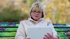 Blonde woman sits on the bench in public garden and uses white tablet computer Stock Footage