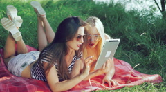 Pretty carefree girls lying on blankets on the grass and using the tablet. 4k - stock footage