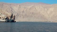 Ship sails along Musandam peninsula, Sultanate of Oman, Gulf of Oman Stock Footage