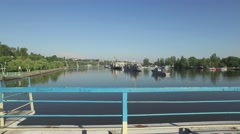 View from the pontoon bridge over river with warships. Day of Ukrainian Navy Stock Footage