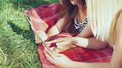 Two carefree girls lying on blankets on the grass and using the tablet. 4k - stock footage