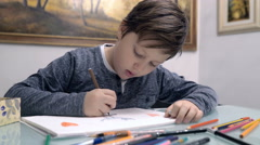 Child focused to complete his drawn - stock footage