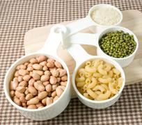 Foods High in Carbohydrate, Raw Pasta, Rice, Peanuts and Mung Beans in Plasti Stock Photos