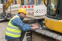 Side view of engineer wearing yellow safety equipment typing on his computer - stock photo