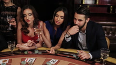 A group of young and beautiful people drink champagne and play casino Stock Footage