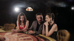 The rich man surrounded by two prostitutes to play and win at the casino Stock Footage
