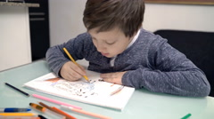 adorable child who draws at the table - stock footage