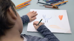 Close up on child's back while draw a cat on a paper Stock Footage